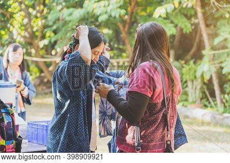 Lamphun Thailand - December 8 :  Unidentified Female Tourist Helps Her Mother To Tie A Scarf On Dece