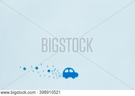 Exhaust Gases Concept. Toy Car On Light Blue Background, With Sequins In Form Of Cloud Of Exhaust Ga