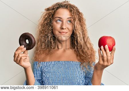 Beautiful caucasian teenager girl holding red apple and donut smiling looking to the side and staring away thinking.