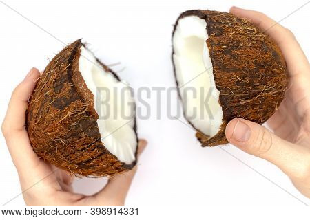 Two Hands Holding Two Halves Of Coconut On A White Background. Fruit Background. Natural Background.