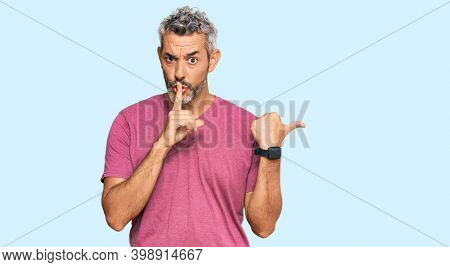 Middle age grey-haired man wearing casual clothes asking to be quiet with finger on lips pointing with hand to the side. silence and secret concept.