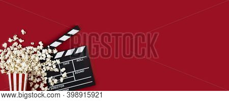 Watching Movie With Popcorn And Clapperboard On Red Background. Movie Goers Accessories, Cinematogra