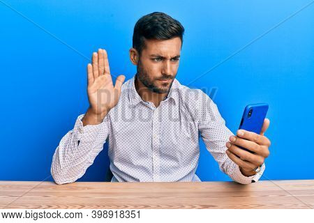 Handsome hispanic man doing video call waving to smartphone skeptic and nervous, frowning upset because of problem. negative person.