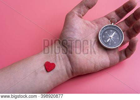The Compass On The Palm Of Your Hand On Pink Background.