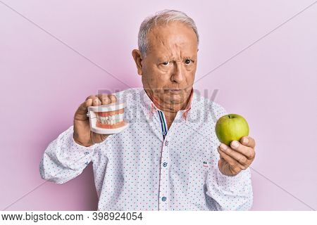 Senior caucasian man holding denture and green apple skeptic and nervous, frowning upset because of problem. negative person.