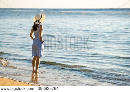 Young Woman In Straw Hat And A Dress Standing Alone On Empty Sand Beach At Sea Shore. Lonely Tourist