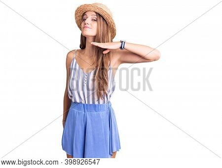 Young beautiful blonde woman wearing summer hat cutting throat with hand as knife, threaten aggression with furious violence