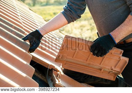 Closeup Of Worker Hands Installing Yellow Ceramic Roofing Tiles Mounted On Wooden Boards Covering Re