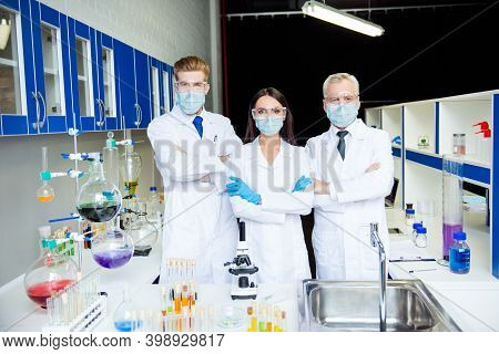 Group Of Three Assistants Doing Vaccine Experiment In Lab All Wearing Labcoats Gloves Glasses Gauze