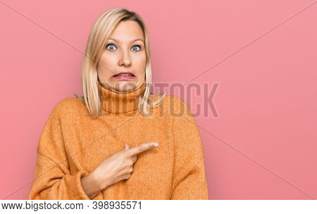 Middle age caucasian woman wearing casual winter sweater pointing aside worried and nervous with forefinger, concerned and surprised expression
