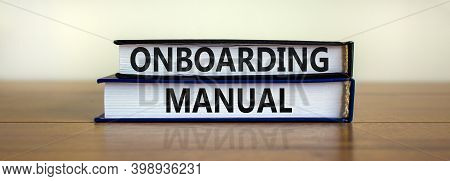 Onboarding Manual Symbol. Books With Words 'onboarding Manual' On Beautiful Wooden Table. White Back