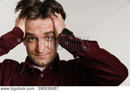 Handsome confused guy grabbing her head and looking at camera isolated over white background