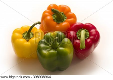 Bright Multi-colored Bell Peppers Lie On A Isolated White Background. Red Peppers, Orange, Yellow An