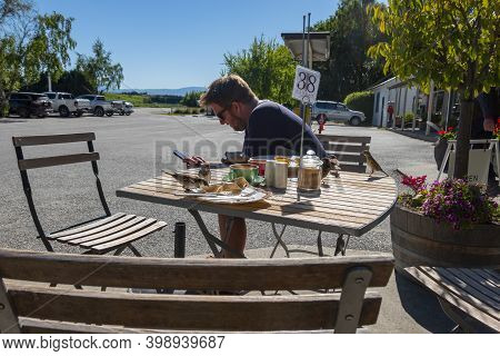 Tarris New Zealand - November 11 2020; Man Sits At Outdoor Café Table Using Mobile Device While Spar
