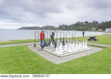 Oban, New Zealand - October 31 2020; Chess Players On Oversized Outdoor Board And Set On Half Moon B