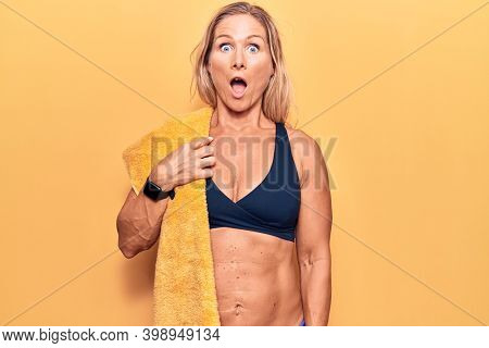 Middle age caucasian blonde woman wearing bikini and towel scared and amazed with open mouth for surprise, disbelief face