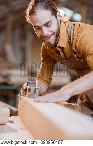 Handsome Carpenter Working With A Wood, Planing A Bar With A Plane In The Carpentry Workshop