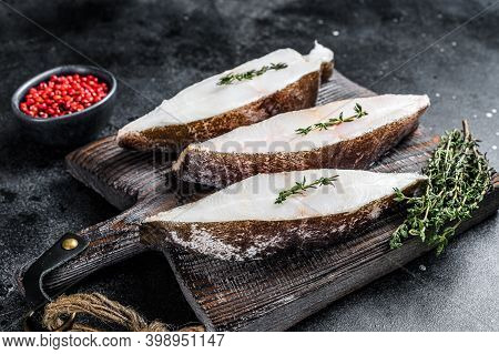 Raw Fresh Halibut Fish Steak On A Wooden Cutiing Board. Black Background. Top View