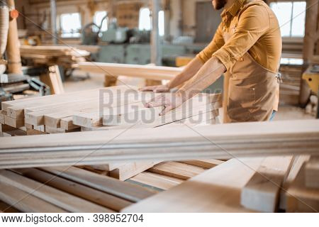 Carpenter Choosing Pine Planks In A Carpentry Workshop Warehouse. Preparing Raw Materials For The Fu
