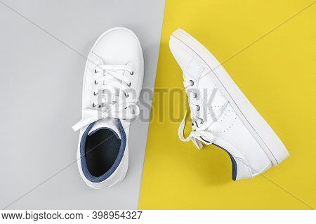 White Sports Shoes, Sneakers With Shoelaces On Yellow And Gray Background. Sport Lifestyle Concept T