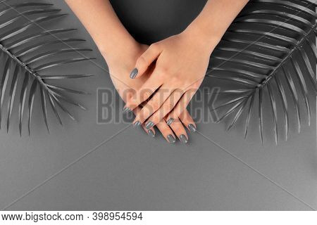 Female Hands With Manicure Of Ultimate Gray Color On Same Color Background
