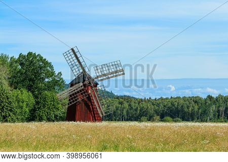 The Typical Red Swedish Windmill Standing In The Fields Full Of Grain. The Rural Landscape Of The Sw