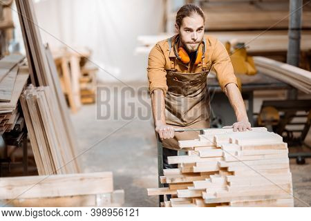Carpentry Worker Pushing Cart Full Of Wooden Planks At The Joinery Warehouse