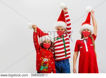 Three Happy Children In Christmas Costumes Hold Up Red Santa Hats In Greeting