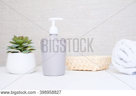 Spa Salon And Bathroom Interior In Pastel Colors, Gray Soap Dispenser, White Towel And Potted Plant