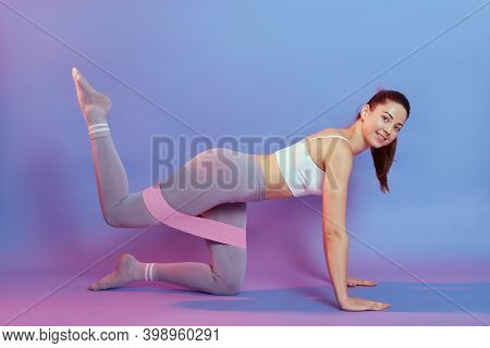 Smiling Sporty Caucasian Woman Has Exercises With Rubber Resistance Band, Trains Buttocks, Raising F