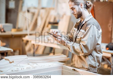 Handsome Carpenter Working On Wooden Carvings Using A Smart Phone At The Carpentry Manufacturing. Co