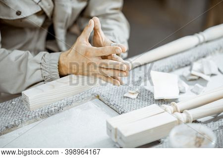 Worker Spackling And Grinding Wooden Balusters At The Work Table At The Manufacturing, Close-up On T