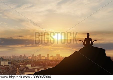 Meditation And Recovery Concept. Woman Sitting In Lotus Position On The Mountain Against The Backdro