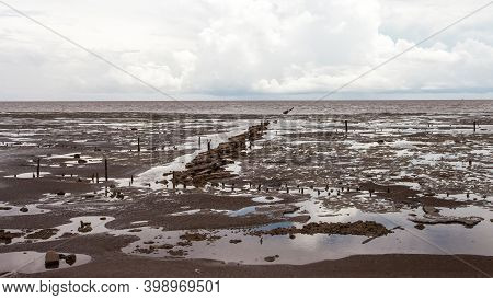 View Of The Ocean Floor After Low Tide With Concrete Fragments Of Buildings Against The Background O