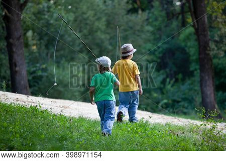 Happy teen boys go fishing on the river, 2 children of the fisherman with a fishing rod on the shore of the lake