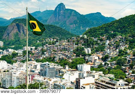 Flag Of Brazil With Favela Babilonia, Leme And Corcovado Of Rio De Janeiro In The Background