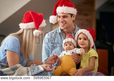 young caucasian dad holding in lap daughter and a baby, smiling, looking at blonde mom, wearing santa hats. christmastime