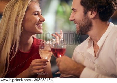 beautiful young caucasian couple in love, celebrating, toasting with wine, looking each other, smiling.