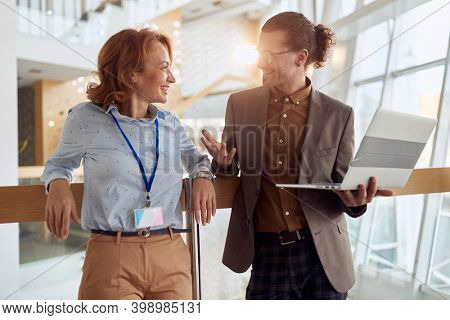 A young colleagues chatting about job at a break at company's hallway in a pleasant atmosphere. People, job, company, business concept.