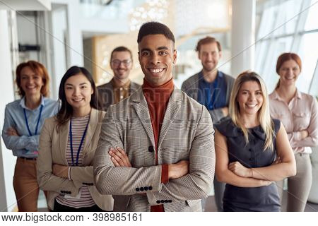 A group of employees posing for a photo at company's hallway in a cheerful atmosphere. People, job, company, business concept.