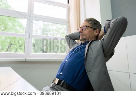 Successful Businessman Leaning Back On A Chair