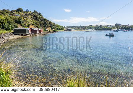 View Across Half Moon Bay To Rustic Boatsheds On Stewart Island.