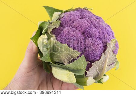 A Violet Cauliflower In A Bag On A Yellow Surface