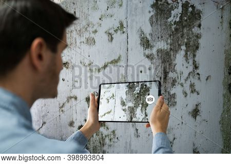 Taking Photo Of Home Wall Mold Damage Using Tablet