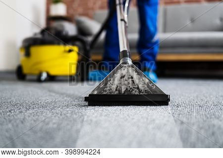 Janitor Cleaning Carpet With Vacuum Cleaner At Home
