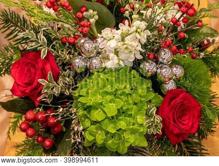 Floral Arrangement In Christmas Colors Including Red Roses, Green Hydrangea, Holly Berries And Silve
