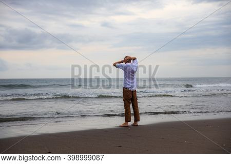 Lonely Man Standing Barefoot On The Beach. Man Wearing Brown Trousers And White Shirt Turned Back To