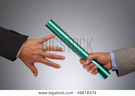 Partnership or teamwork concept two businessmen handing over a baton