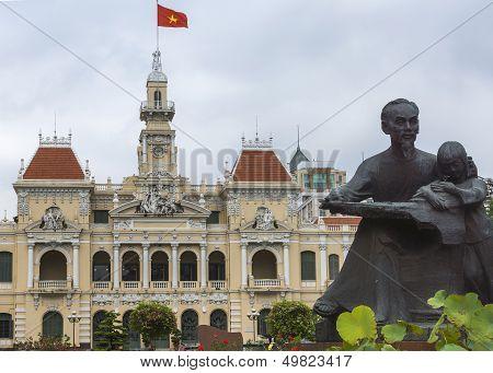 Ho Chi Minh Statue And Saigon City Hall With Flag.