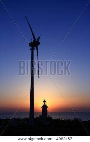 A Lighthouse A Wind Turbine And A Sunset